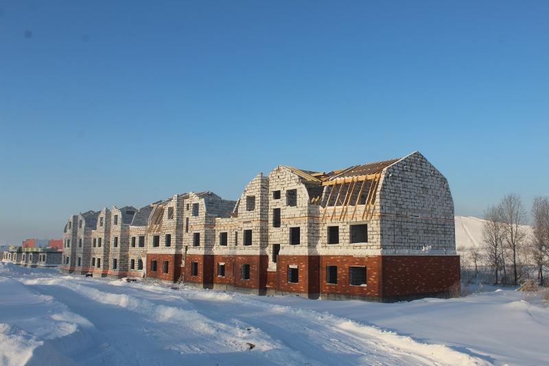 Многоквартирный дом по адресу: квартал Согласия, 1.  Вид на главный фасад. Монтируем стропила на кровле.